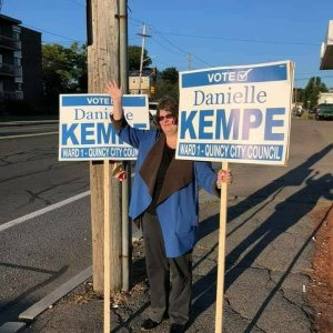 Danielle Kempe in a blue blazer holding 2 Danielle Kempe for Quincy signs and waving